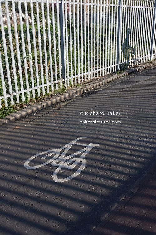 A commuting cyclist rides alongside sunlit railings on a backroad in Kennington, South London.