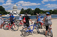WASHINGTON - JUNE 30, 2019: A tour group on bicycles stop in front of the U.S. Capital building near the Capital Reflecting Pool on June 30, 2019, in Washington, D.C.