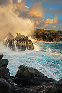 Waves crashing against coastal lava rocks at sunset at The End of the World, Maihi Bay, near Keauhou, North Kona District, Big Island, Hawaii