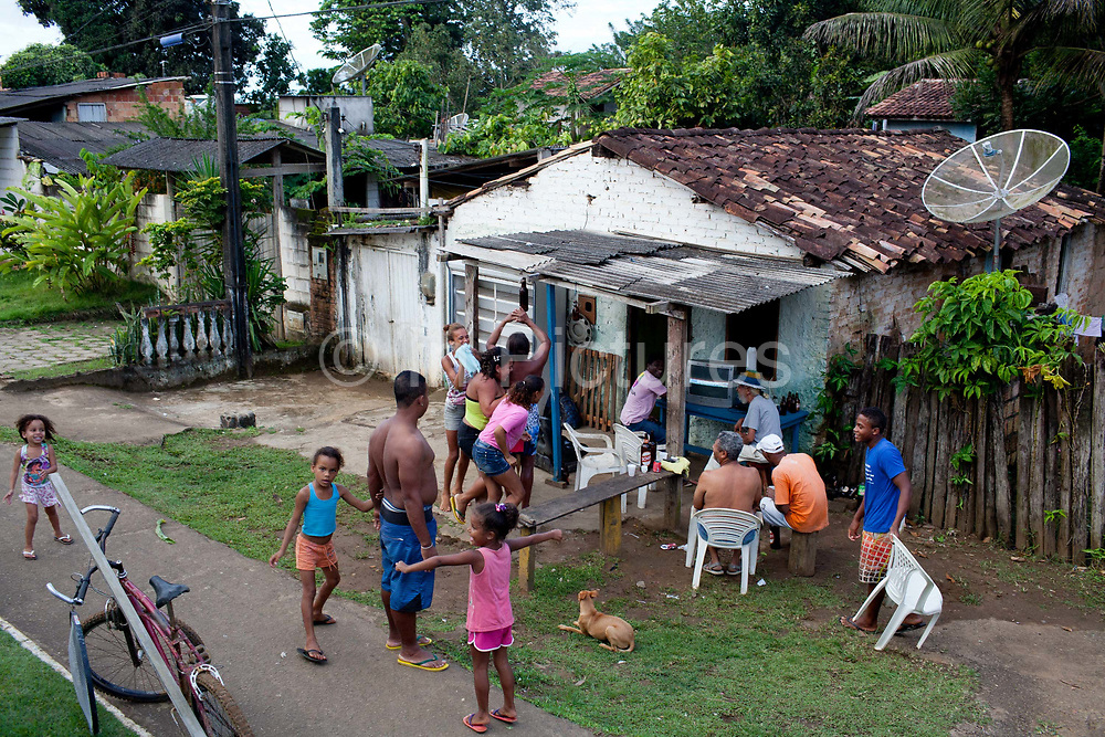 Brazil football fans with families watching a football game on the television, in a rural setting, clapping and engaged with the television. Bahia, Brazil