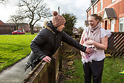 A neighbour touches the stomach of a young pregnant mother outside her house on a council estate in Leyland, Lancashire.