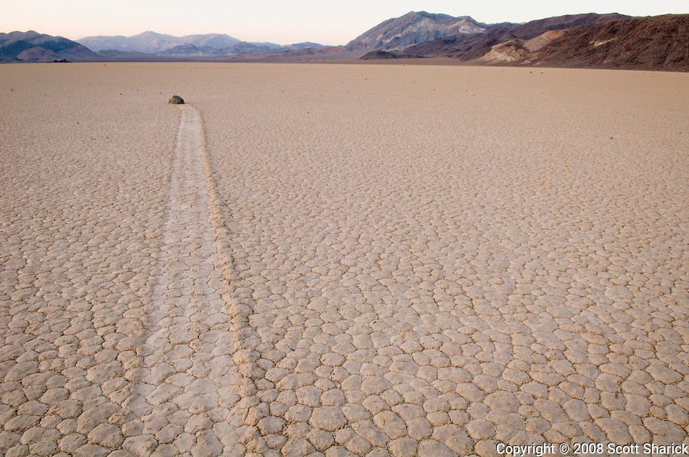 A single rock sits on the playa at the Racetrack in Death Valley National Park. A track shows where the rock moved along the floor of the valley - a phenomenon that is yet unexplained.