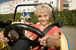 Smiling boy in vehicle on driver training area