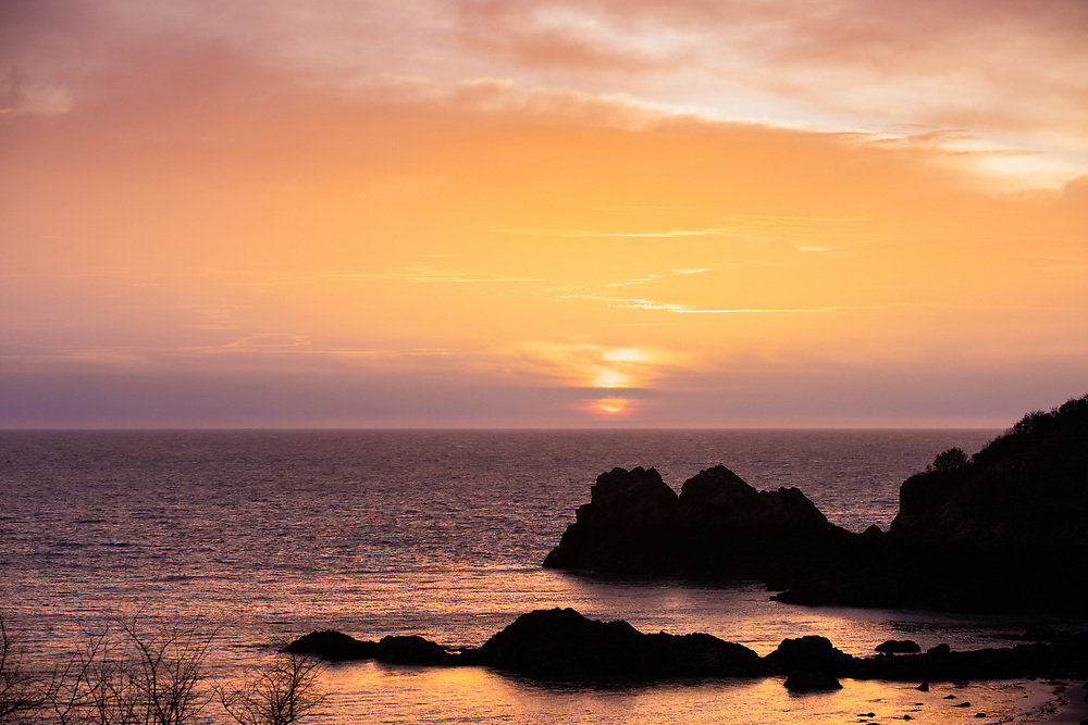 Sun rising over the horizon line and reflecting orange on the sea at Archirondel beach on the east cost of Jersey, Channel Islands