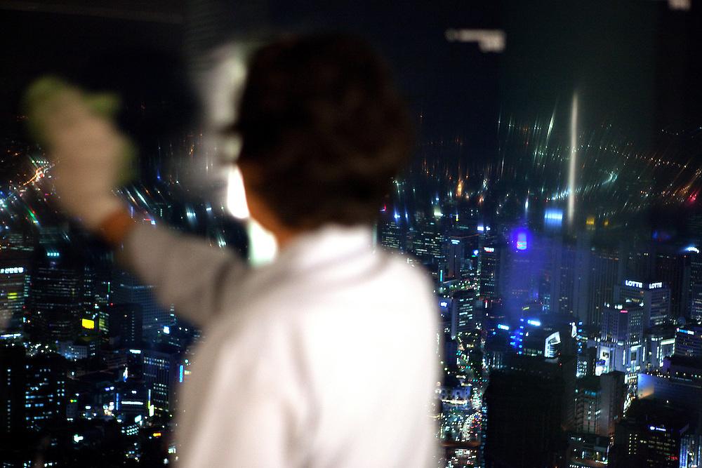 Frau reinigt die Fenster auf der oberen Aussichtsplattform des N Seoul Towers. Der N Seoul Tower ist ein der ÷ffentlichkeit zug‰nglicher Fernsehturm in der s¸dkoreanischen Hauptstadt Seoul. Der 236,7 Meter hohe Turm steht auf 243 m ¸. N.N. des Berges Namsan. <br /> <br /> Woman cleaning windows of the observation deck of N Seoul Tower in the Korean metropolis.N Seoul Tower is a communication tower located in Seoul, South Korea. Built in 1969, and opened to the public in 1980, the tower measures 236.7 m (777 ft) in height (from the base) and tops out at 479.7 m (1,574 ft) above sea level.