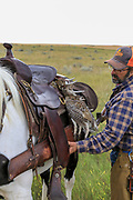 John Zeman returns his shotgun to its scabbarde during a Montana horseback grouse hunt.
