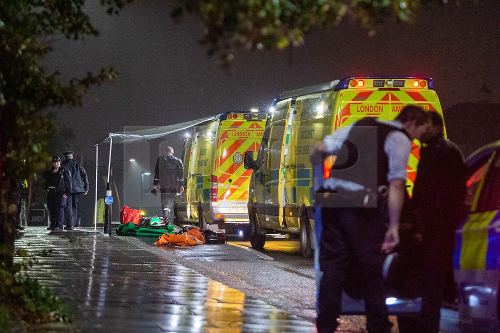 © Licensed to London News Pictures. 08/10/2020. London, UK. Police and paramedics stand next to London Ambulance Service incident response vehicles. At approximately 21:15BST a male was seen to enter the water near Ferry Road in Tottenham following a police pursuit from the Hackney / Tower Hamlets area of a number of males riding mopeds. Emergency services attended and a large scale search was launched. Photo credit: Peter Manning/LNP