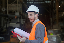Young male engineer holding blueprint and using digital tablet at construction site, Freiburg Im Breisgau, Baden-Wuerttemberg, Germany