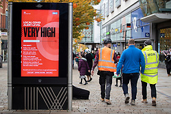 © Licensed to London News Pictures. 25/10/2020. Manchester, UK. Workers walk past a covid very high alert level sign on Market Street, Manchester. Shoppers in Manchester aren't deterred by new tier 3 restriction or potential tier 4 restrictions, which could see retail and restaurants closed. Photo credit: Kerry Elsworth/LNP