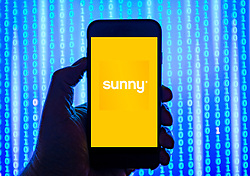 Person holding smart phone with  Sunny payday loans company  logo displayed on the screen. EDITORIAL USE ONLY