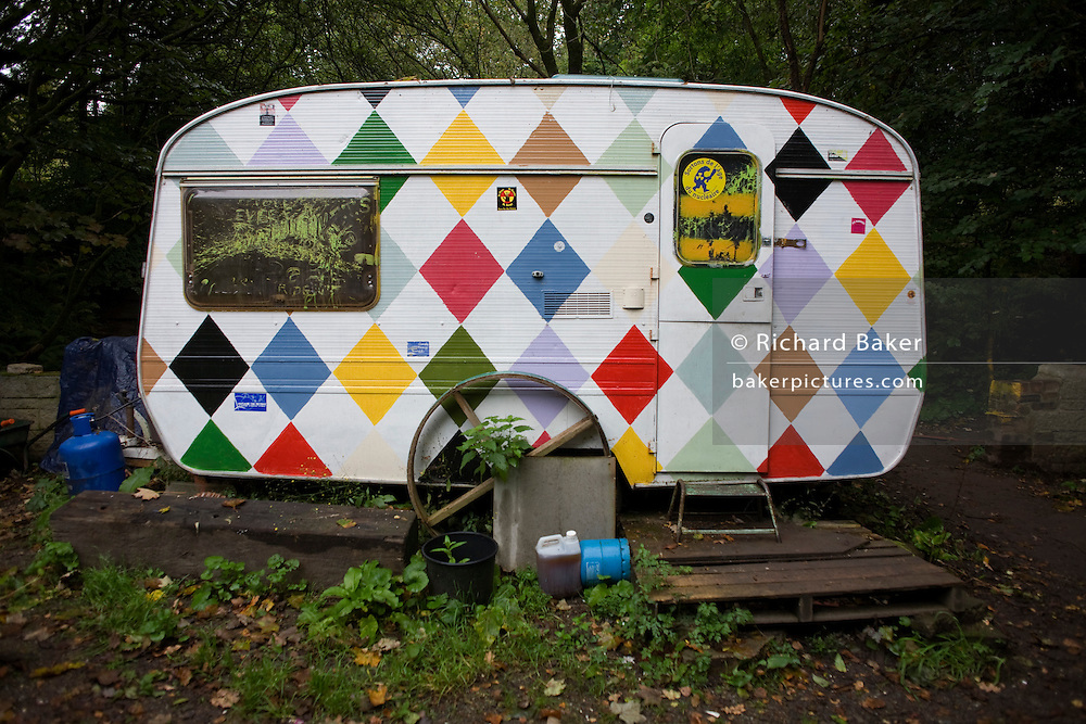 A customized caravan sits in the damp woods at the Faslane Peace Camp, Argyll and Bute, Scotland. Matt Bury, 52, is one of the camp's 10 full time residents and has been living in this trailer for a year. Painted harlequin-styled diamonds adorn the walls of the van in a personal artistic statement. Calor gas bottles lie on the ground and weeds grow around this semi-permanent site. Faslane Peace Camp is a makeshift political activists' site alongside HM Naval Base Clyde where Trident nuclear deterrent missiles and Vanhuard Class submarines dock. The camp has been occupied continuously, in a few different locations since 12 June 1982. Image taken for the 'UK at Home' book project published 2008.
