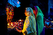 2nd April 2015, New Delhi, India. Women pray at a shrine dedicated to Djinn worship in the ruins of Feroz Shah Kotla in New Delhi, India on the 2nd April 2015<br /> <br /> PHOTOGRAPH BY AND COPYRIGHT OF SIMON DE TREY-WHITE a photographer in delhi<br /> + 91 98103 99809. Email: simon@simondetreywhite.com<br /> <br /> People have been coming to Firoz Shah Kotla to leave written notes and offerings for Djinns in the hopes of getting wishes granted since the late 1970's. <br /> Feroz Shah Tughlaq (r. 1351–88), the Sultan of Delhi, established the fortified city of Ferozabad in 1354, as the new capital of the Delhi Sultanate, and included in it the site of the present Feroz Shah Kotla. Kotla literally means fortress or citadel. The pillar, also called obelisk or Lat is an Ashoka Column, attributed to Mauryan ruler Ashoka. The 13.1 metres high column, made of polished sandstone and dating from the 3rd Century BC, was brought from Ambala in 14th century AD under orders of Feroz Shah. It was installed on a three-tiered arcaded pavilion near the congregational mosque, inside the Sultanate's fort. In centuries that followed, much of the structure and buildings near it were destroyed as subsequent rulers dismantled them and reused the spoil as building materials.
