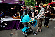 Man with pram. Borough Market is a thriving Farmers market near London Bridge. Saturday is the busiest day.