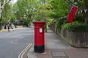 On the 75th anniversary of VE Day Victory in Europe Day, the official end of WW2 and during the UKs Coronavirus pandemic lockdown, two runners jog towards a heritage Royal Mail post box and a naval ensign flag that hangs from the garden of a corner property in Camberwell, on 8th May 2020, in London, England.