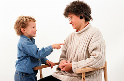 Young boy using sign language to communicate with mother with hearing impairment,