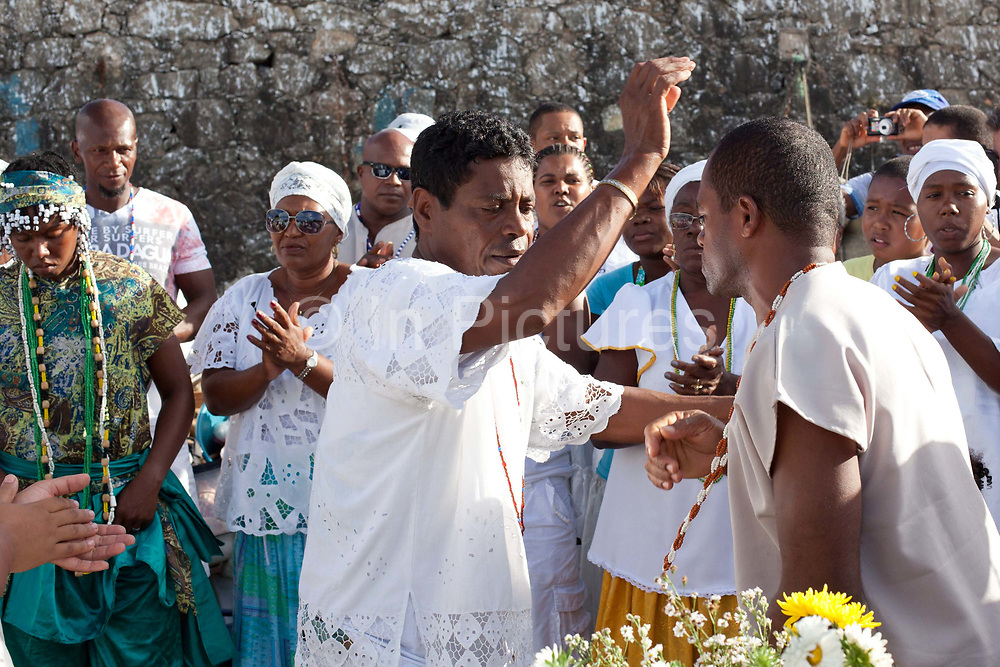 Young man being blessed by a male Babalowo Priest, Candomble group in traditional white dress taking part in a public ceremony on the beach. February 2nd is the feast of Yemanja, a Candomble Umbanda religious celebration, where thousands of adherants visit the Rio Vermehlo Red River to make offerings of flowers and prayers, paying their respects to Yemanja, the Orixa goddess of the Sea and water.
