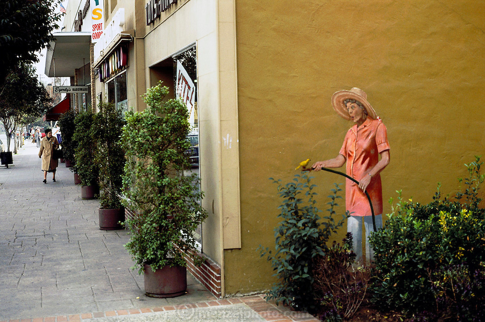 Mural of a woman watering plants, with a bird sitting on the hose.  Downtown Palo Alto, California. USA.