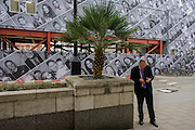 A businessman texts a message alongside a palm and in front of a City construction hoarding featuring dozens of London faces.