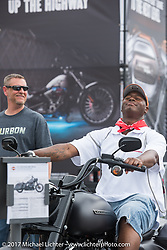 Goldie Calhoun of Ocala, FL trys out the new 2017 Road King Special at the Harley-Davidson display at the Daytona Speedway during Daytona Bike Week. Daytona Beach, FL. USA. Monday March 13, 2017. Photography ©2017 Michael Lichter.