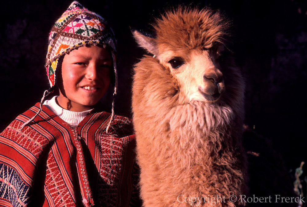 PERU, PORTRAITS a young Quechua boy dressed in traditional  hat and serape with his pet a young alpaca near Cuzco