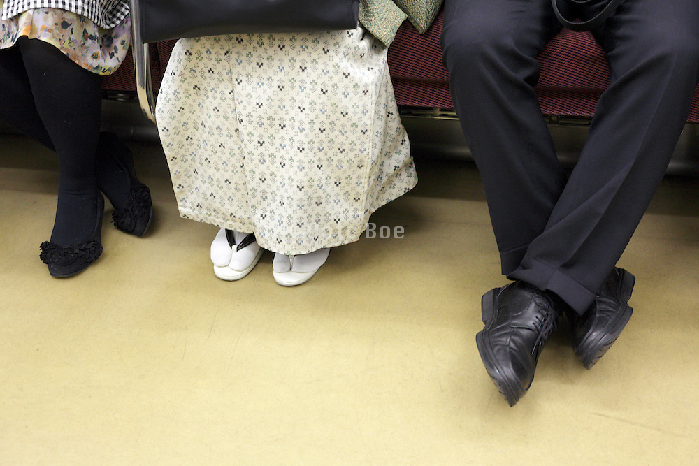 in traditional kimono woman sitting during train commute between two today style dressed people