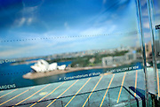The names of places of interest are etched into a glass panel around the 87 metre high Sydney Harbour Bridge Pylon Lookout. Arrows engraved into copper cladding point out those locations. In this view, the Sydney Opera House is in the background. Sydney, Australia
