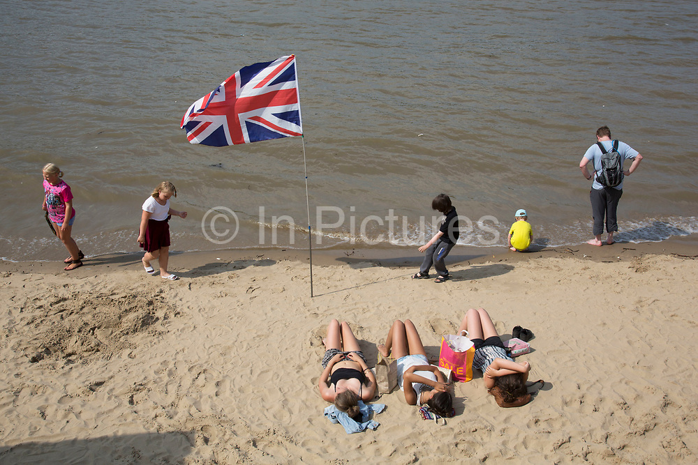 Three girls sunbathing on the River Thames beach on the Southbank, London, UK. At low tide this sandy area becomes almost like a coastal gathering spot with people using the water's edge as if the seaside. The South Bank is a significant arts and entertainment district, and home to an endless list of activities for Londoners, visitors and tourists alike.