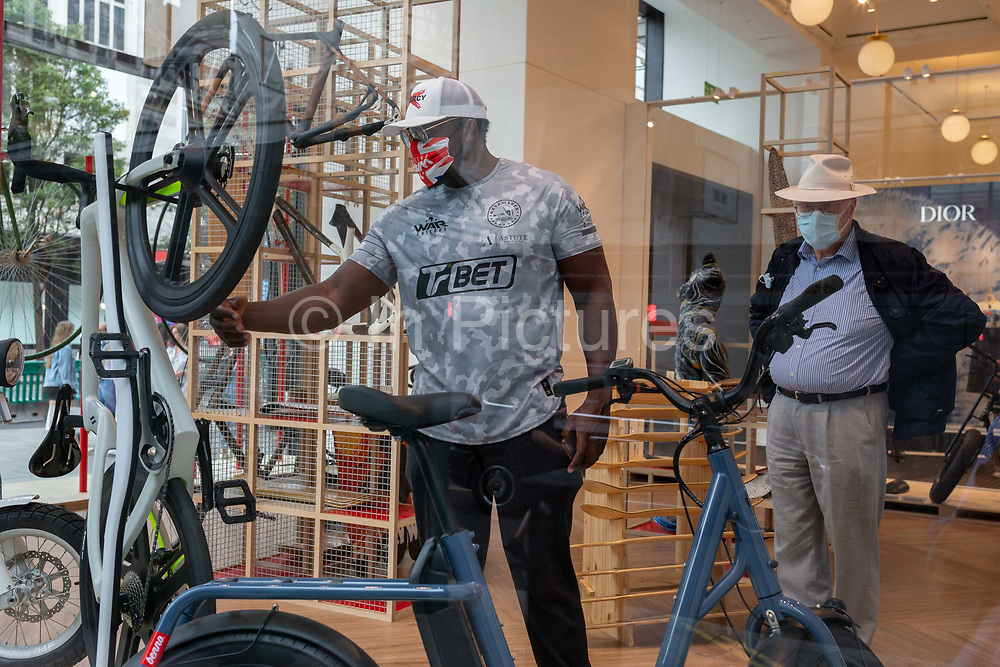 On the day that covid pandemic guidelines for shoppers in England mean that the wearing of face coverings in shops is mandatory, shoppers wearing face masks look at bikes and cycling products in the window of Selfridges on Oxford Street, on 24th July 2020, in London, England.