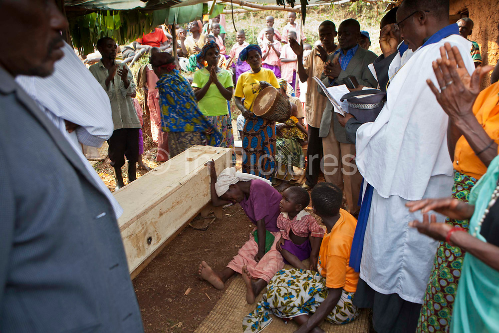 Locals from the Batwa tribe community gather with the family around the coffin for the funeral of Matale, a local woman who died of cancer.