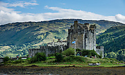 Eilean Donan Castle, in Kintail National Scenic Area, Scotland, United Kingdom, Europe. This picturesque island stronghold sits where three sea lochs meet at the village of Dornie in the western Highlands (Loch Duich, Loch Long, and Loch Alsh). Since restoration of the 1200s castle in the early 1900s, a footbridge connects the island to the mainland. The island is named after Donnán of Eigg, a Celtic saint martyred in 617. The castle was founded in the 1200s and became a stronghold of the Clan Mackenzie and their allies the Clan Macrae. In the early 1700s, the Mackenzies' involvement in the Jacobite rebellions led in 1719 to the castle's destruction by government ships. Lieutenant-Colonel John Macrae-Gilstrap's 1920-32 reconstruction of the ruins made the present buildings.