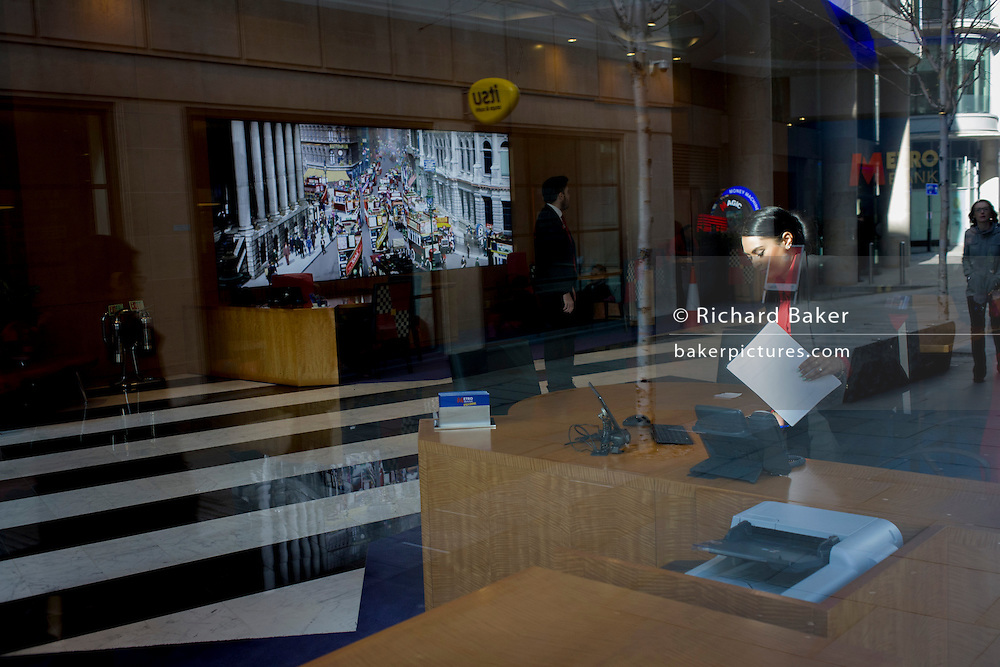 A lady Metro Bank worker and foyer featuring a vintage photo of City traffic seen through a front window.