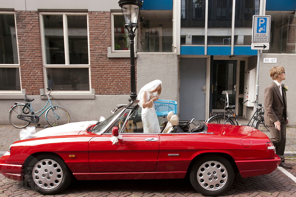 Een bruidspaar wacht bij hun trouwauto.<br /> <br /> A bride and groom are waiting next to their car.