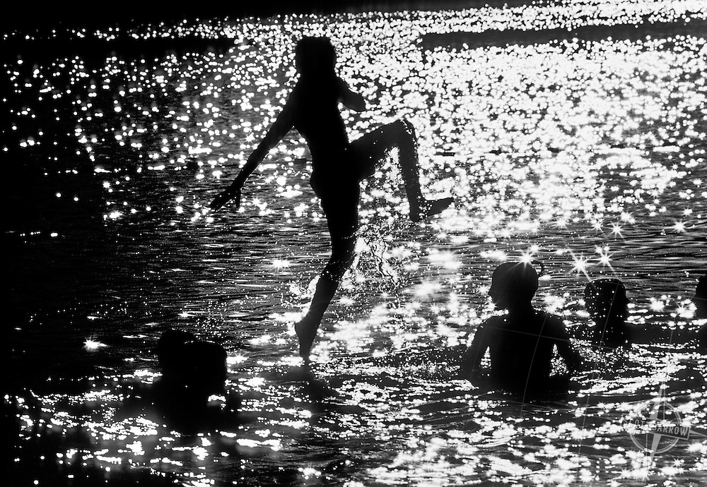 Boy jumping into lake with friends