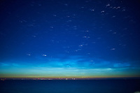 Noctilucent Clouds Over the Baltic Sea. From my cabin on the MV Explorer while traveling from Stockholm to Copenhagen. Composite of 27 images taken with a Nikon D4 camera and 28 mm f/1.8 lens (ISO 800, 28 mm, f/1.8, 1 sec). Raw image processed with Capture One Pro, and Photoshop CC (statistics, maximum).