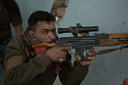Licensed to London News Pictures. 01/04/2017. Mosul, Iraq. An Iraqi Federal Police sniper takes searches for Islamic State fighters with his rifle in West Mosul, Iraq, today (01/04/2017). Iraqi forces continue to fight house to house as they push further into West Mosul. Iraqi forces are now advancing on the city's old districts where Islamic State fighters still hold out. Photo credit: Matt Cetti-Roberts/LNP