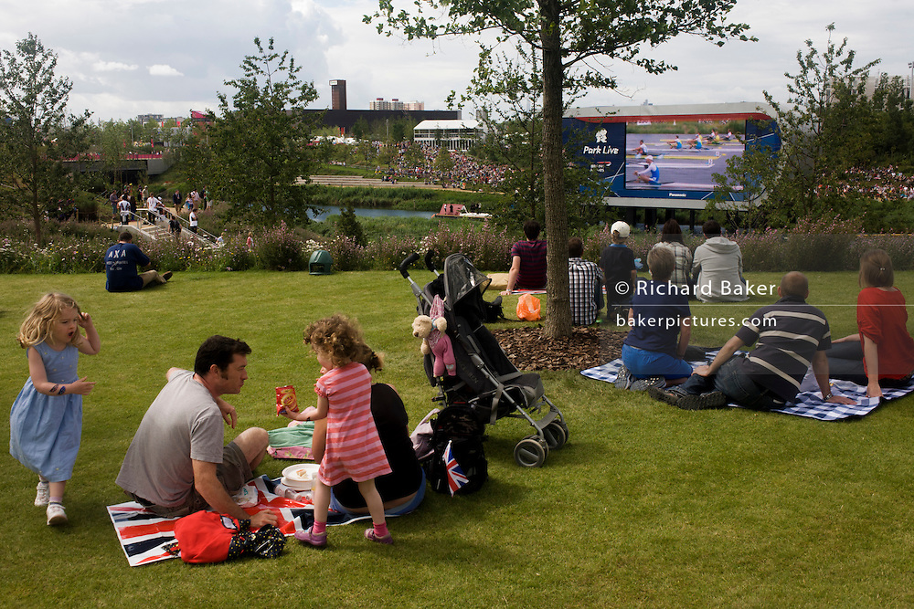 Families and spectators watch a televised rowing race on the grass in the Olympic Park during the London 2012 Olympics. The planting of 4,000 trees, 300,000 wetland plants and more than 150,000 perennial plants plus  nectar-rich wildflower make for a colourful setting for the Games. This land was transformed to become a 2.5 Sq Km sporting complex, once industrial businesses and now the venue of eight venues including the main arena, Aquatics Centre and Velodrome plus the athletes' Olympic Village. After the Olympics, the park is to be known as Queen Elizabeth Olympic Park.