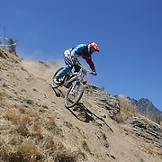 Tyler Perrin from Palmerston North in action during the New Zealand South Island Downhill Cup Mountain Bike series held on The Remarkables face with a stunning backdrop of the Wakatipu Basin. 150 riders took part in the two day event. Queenstown, Otago, New Zealand. 9th January 2012. Photo Tim Clayton
