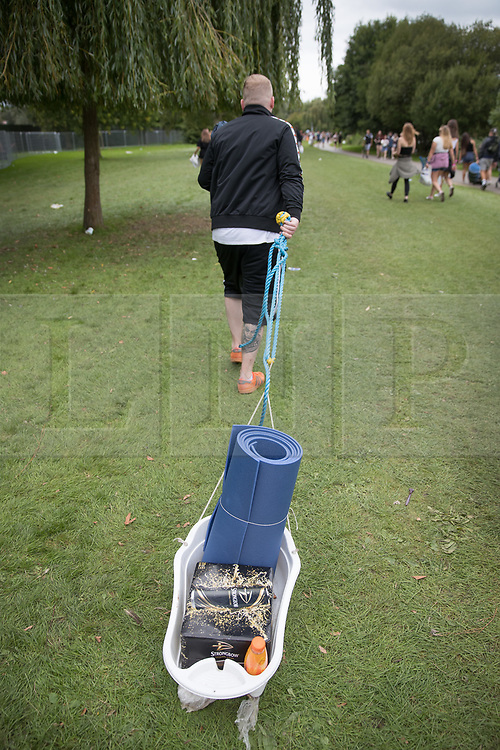 © Licensed to London News Pictures. 24/08/2017. Reading, UK. A music fan drags his supplies to Reading Festival in a plastic bowl. The weather is expected to stay fine for the start of the three day music festival. Photo credit: Peter Macdiarmid/LNP