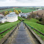 Steps leading to the top of the Lion's Mound (Butte du Lion), an artificial hill built on the battlefield of Waterloo to commemorate the location where William II of the Netherlands was injured during the battle. The hill is situated on a spot along the line where the Allied army under the Duke of Wellington's command took up positions during the Battle of Waterloo. The white cylindrical building is the Panorama, while construction of other buildings is going on in anticipation of the 200th anniversary in June 2015.