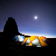 Tents at the Lava Tower Camp at night, with clear stars. The rock formation at left is the silhouette of Lava Tower. The sun has only recently gone below the horizon and is still partly lighting up the very low sky.
