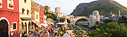 Wide panorama of the busy old market bazaar street Kujundziluk with lots of tourist craft and art shops and street merchants. Sunset late afternoon light. View along the river of the old reconstructed bridge. Restaurants cafes along the river bed. Historic town of Mostar. Federation Bosne i Hercegovine. Bosnia Herzegovina, Europe.
