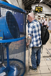 © Licensed to London News Pictures. 26/07/2018. London, UK. Passengers on the London Underground cool off in front of a large fan in Bank tube station during hot weather. Today is predicted to be the hottest day of the year, with temperatures in the capital set to rise up to 35 degrees, as the UK experiences a prolonged heatwave. Photo credit : Tom Nicholson/LNP