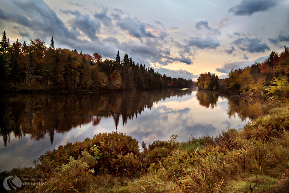 A beautiful autumn day in New Hampshire with a perfect mirrored reflection in a pond along Highway 110, just north of Berlin, New Hampshire.