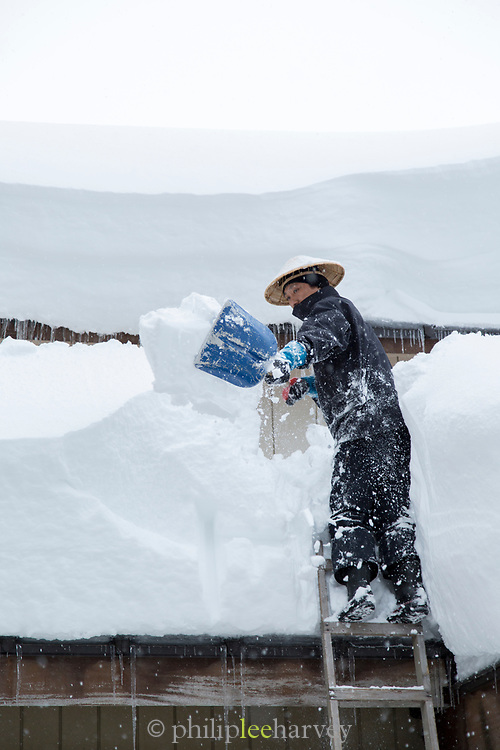 Man standing on ladder removing snow from roof of building, Nozawaonsen, Japan