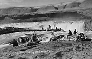 9305-B7339. Indians fishing the channel between Standing and Cheif's islands, Celilo Falls. The photographer is on Standing island, across the channel is Chief's Island, behind that is the main falls at Celilo. Ateem island (later Albert Brothers island) is on the extreme right. ca. 1928