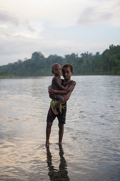Stesie holds a toddler named Yagang at sunset while standing in the Clay River in the village of Likan, located in East Sepik Province in Papua New Guinea.<br /> <br /> (June 24, 2019)
