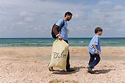 Israel Beach cleaning. Volunteers scan a beach collecting garbage