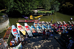 © Licensed to London News Pictures. 19/07/2016. Oxford, UK. A row of colourful punts wait on the River Cherwell in the grounds of Oxford University in Oxfordshire, on what is due to be the hottest day of 2016 so far, with temperatures possibly hitting the mid 30's.  Photo credit: Ben Cawthra/LNP