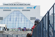 """An activist from the Palestine Action activist group is seen climbing a fence outside Abu Dhabi National Exhibition Centre Excel in East London on Sunday, Sept 12, 2021. Activists are targeting an arms fair hailed as """"the world's largest gathering of the defence and security community"""". (VX Photo/ Vudi Xhymshiti)"""