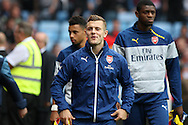 Jack Wilshere of Arsenal enjoys a wry smile as he makes his way to the bench before kick off. Barclays Premier league match, Aston Villa v Arsenal at Villa Park in Birmingham on Saturday 20th Sept 2014<br /> pic by Mark Hawkins, Andrew Orchard sports photography.